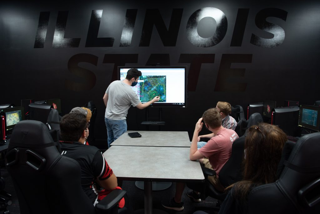 Redbird Esports players look at a touchscreen in The Vault