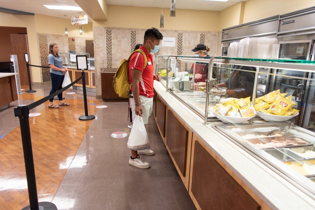Micor waits for his food to be served into to-go containers at the Watterson Dining Commons.
