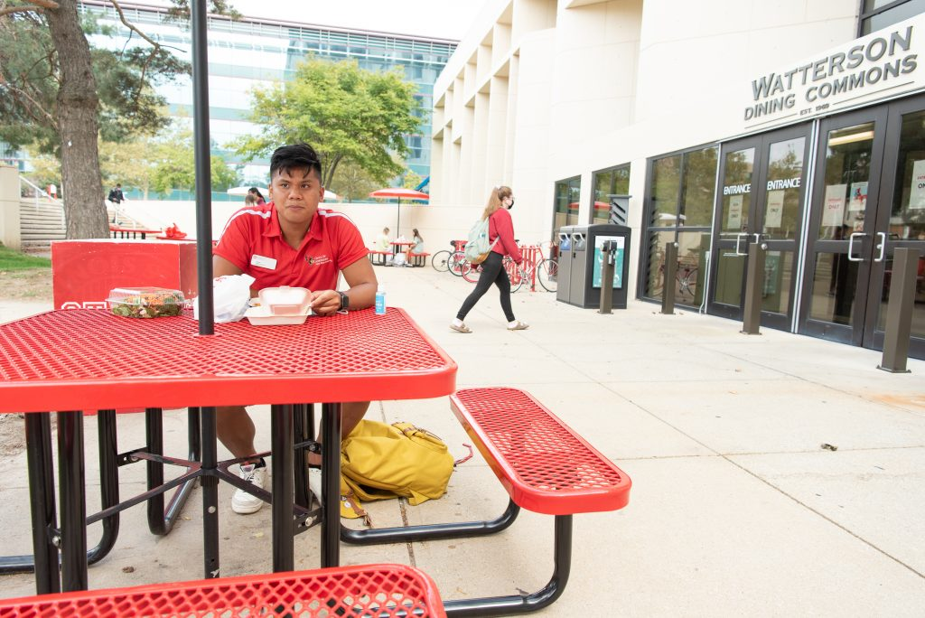 Micor eats lunch at a picnic table outside of the Watterson Dining Commons.
