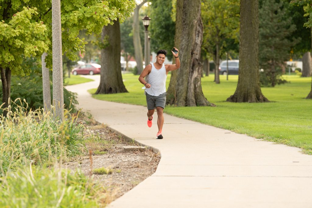 Micor waves to a friend as he runs through People's Park on his two-mile run from his apartment to Watterson Towers.