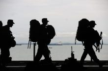 Military soliders walking by water with backpacks on and holding gear. The picture is in black and white.