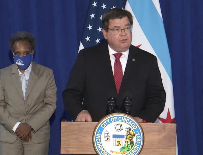 man at podium with woman standing behind him
