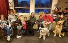 College mentors and elementary school mentees pose with four dogs