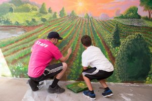 IAS staff painting mural with youth