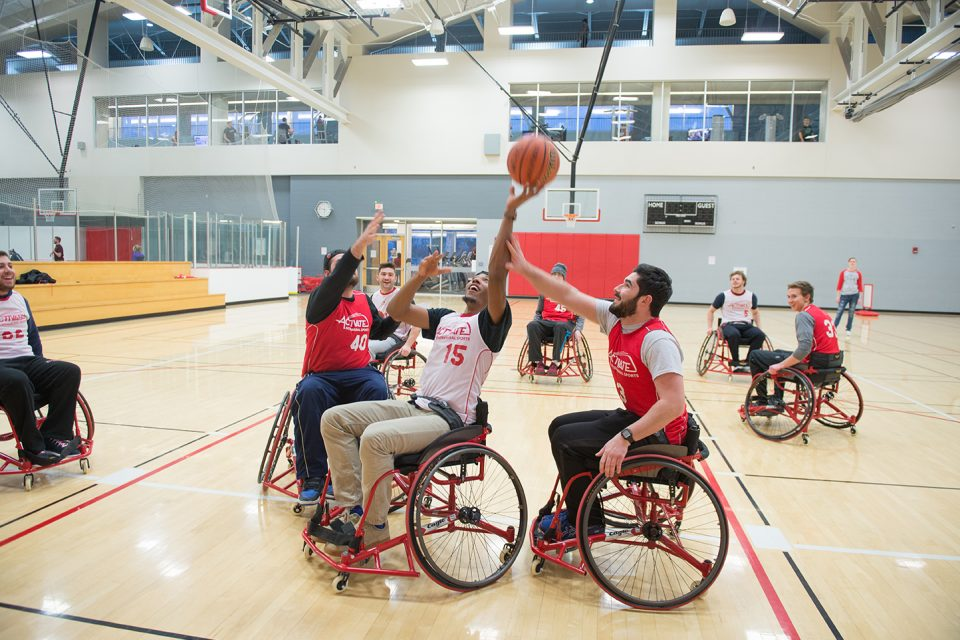 students playing basketball in wheelchairs on a court