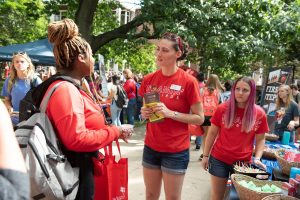 Representative of Roamin' Redbirds speaking with a student at Festival ISU